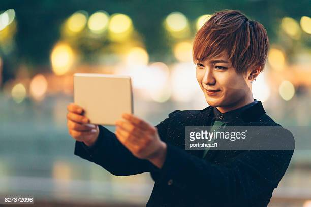 Man making selfie with digital tablet on street at night