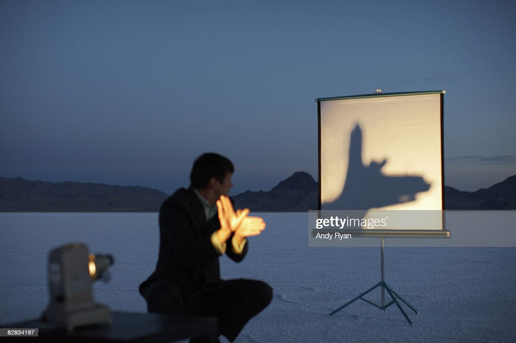 Man Making Shadow Puppet on Screen in Desert : Stock Photo