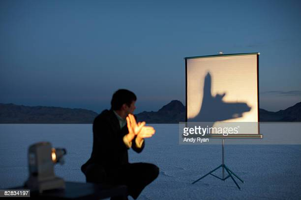 Man Making Shadow Puppet on Screen in Desert