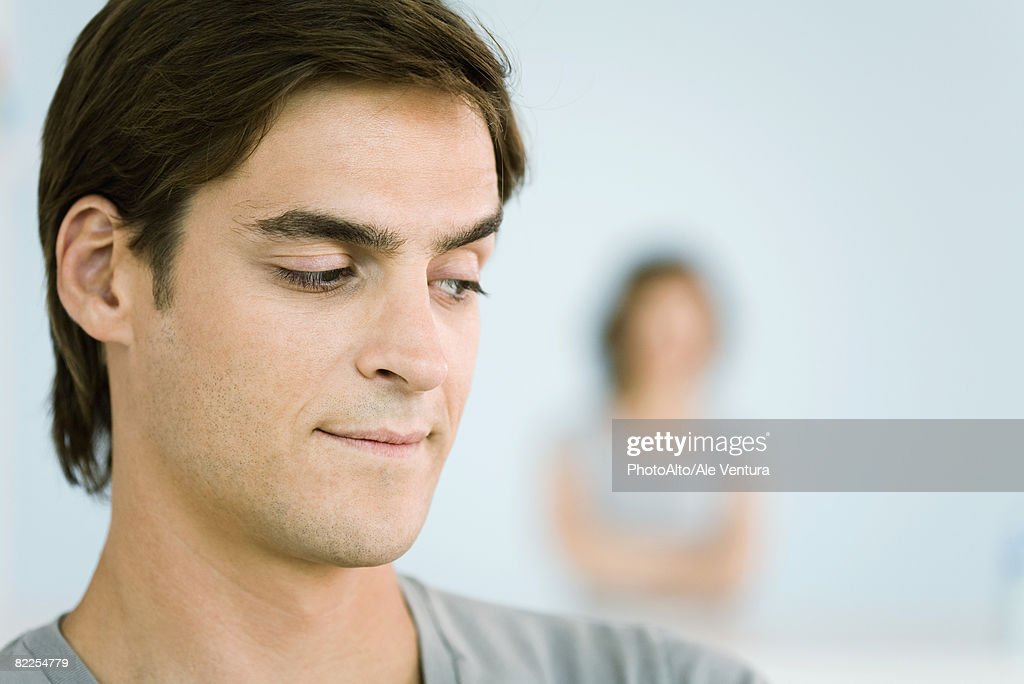 Man making sideways glance over shoulder, woman with arms folded in background : Stock Photo