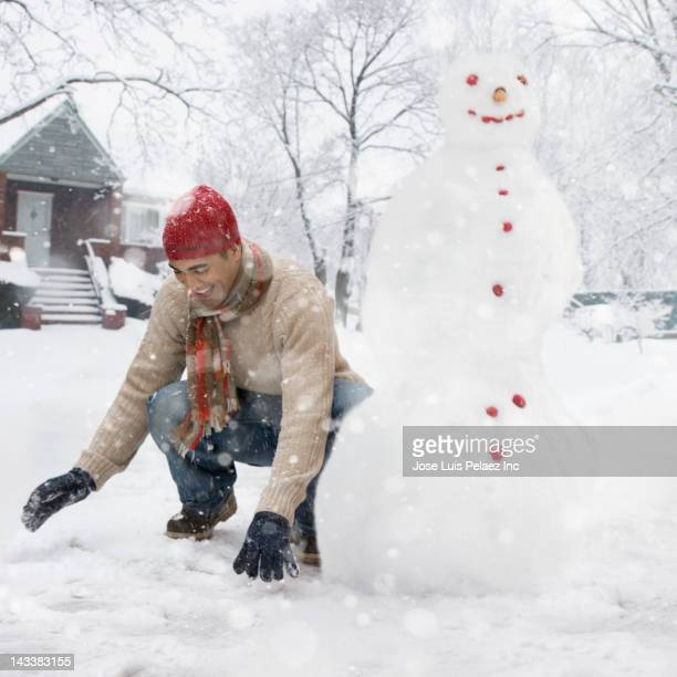 Man making snowman in front yard
