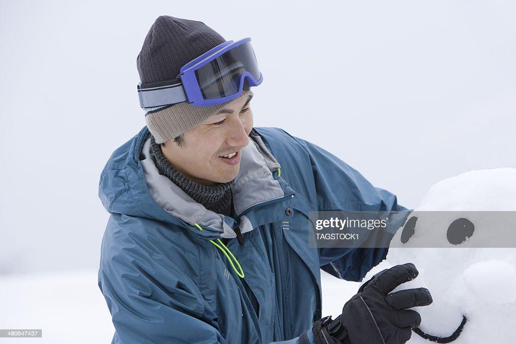 Hombre haciendo muñeco de nieve : Foto de stock