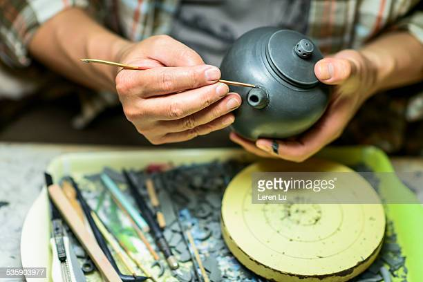 Man making traditional teapot