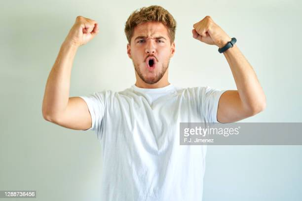 man making triumph gesture in front of white wall - white shirt stock pictures, royalty-free photos & images