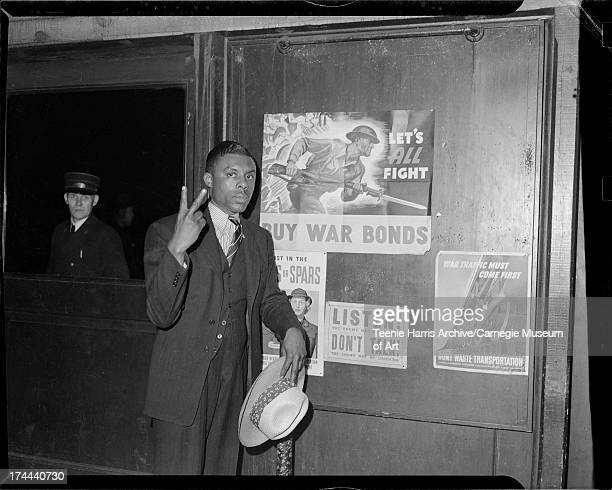 Man making V sign outside railroad station for Double V campaign Pittsburgh Pennsylvania c 1943