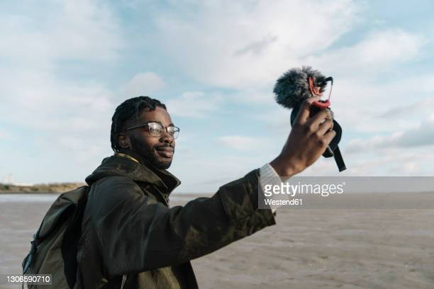 man making vlog of himself at beach against sky - the media stock pictures, royalty-free photos & images