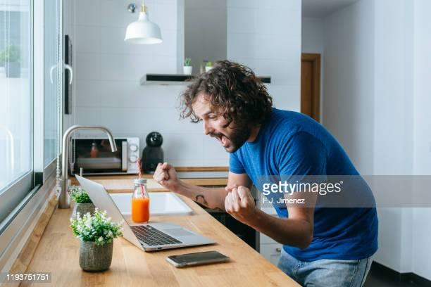 man making with triumph gesture - ganar fotografías e imágenes de stock