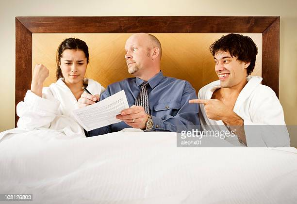 Man Making Woman Sign Legal Papers in Bed
