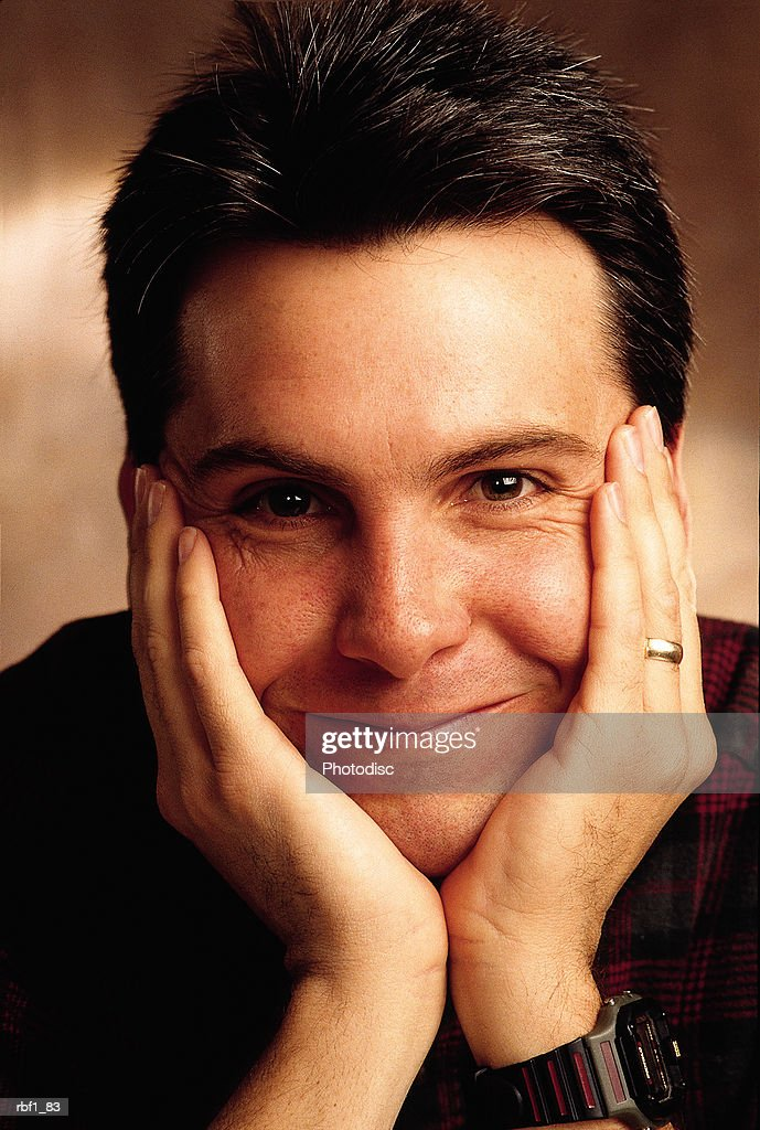 man male with dark hair wearing a dark shirt rests his chin on his hands and smiles slightly : Stockfoto