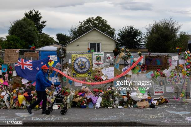 A man man walks past flowers and tributes displayed in memory of the twin mosque massacre victims along the road outside the Linwood mosque in...