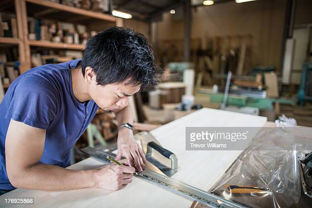 A man marking and measuring a piece of wood