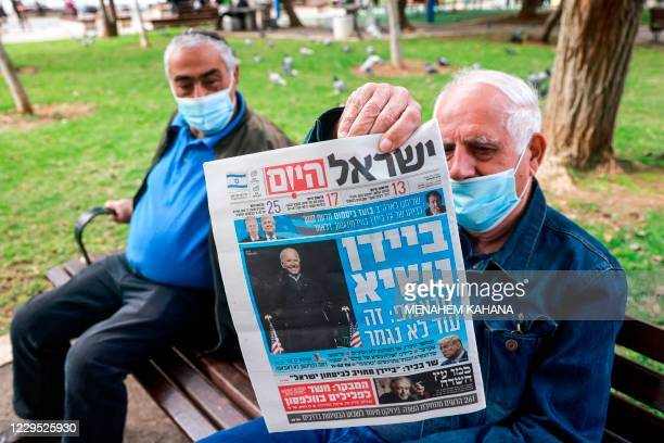 Man, mask-clad due to the COVID-19 coronavirus pandemic, holds up a copy of Israeli newspaper Israel Hayom declaring Joe Biden as president-elect and...