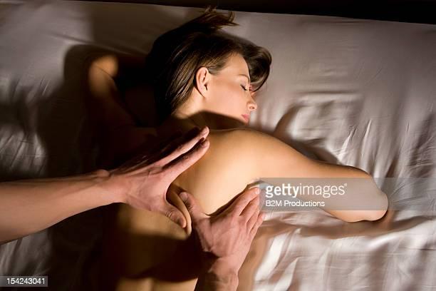 a man massaging a woman's back in bed - massaggio sensuale foto e immagini stock