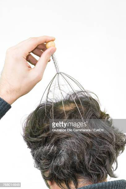 man massaging head with equipment against white background - head massage stock photos and pictures