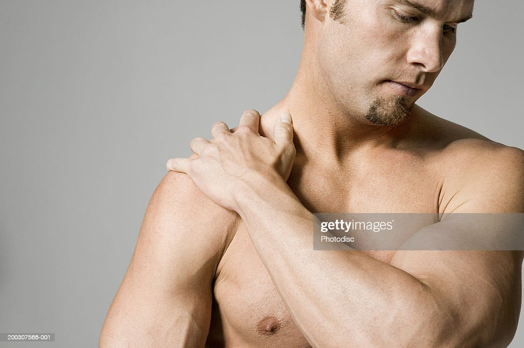 Man massaging shoulder : Stock Photo