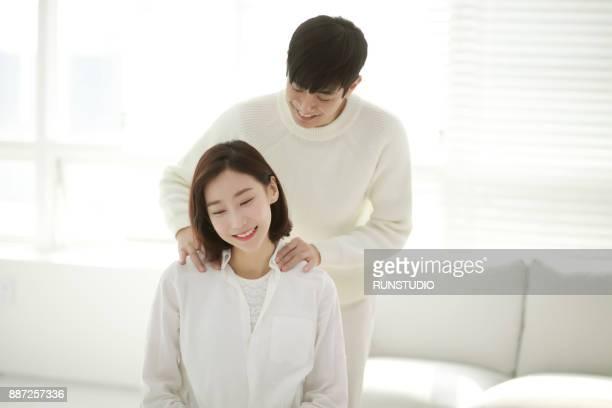 Man massaging  woman shoulder in living room