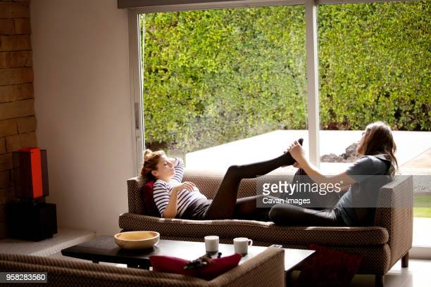 man massaging womans feet lying on sofa at home - beau pied homme photos et images de collection