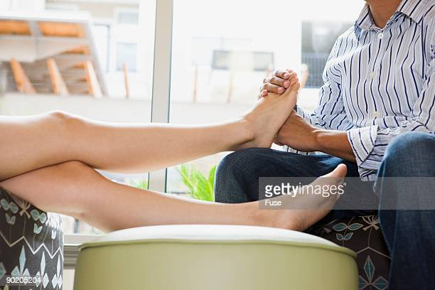 man massaging woman's feet - husband massage wife stock photos and pictures