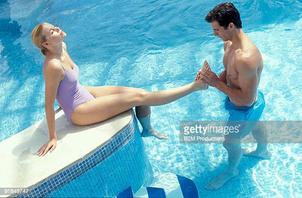 Man massing woman by swimming pool