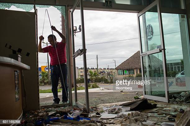 A man measure a broken window frame at the Guadalajara Pharmacy after looting in Veracruz City Mexico on Saturday Jan 7 2017 Mexico's National...
