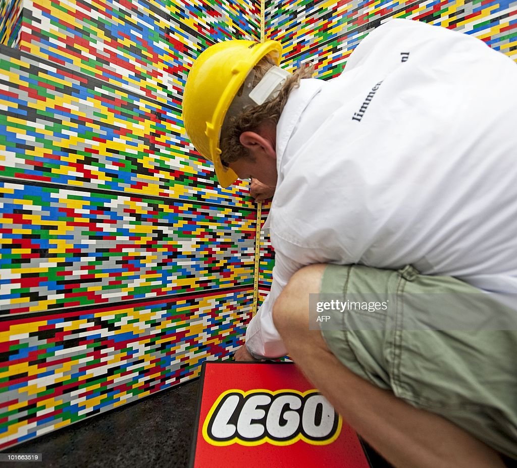 A man measures a tower created from lego bricks in the Dutch town of Limmen, some 4O kms northwest of Amsterdam, on June 6, 2010. The Lego tower measures 30.52 meters, breaking the previous record for the largest Lego tower - set in Oslo, Sweden - by 30 cms.