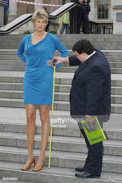 A man measures Svetlana Pankratova's legs the longest legs belonging to a woman at 132 cm as she and He Pingping the world's smallest man at 7461 cm...