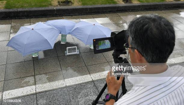 A man measures the surface temperature of a watered road with parasols in Tokyo on Aug 13 2018 The experiment was conducted by the Tokyo government...