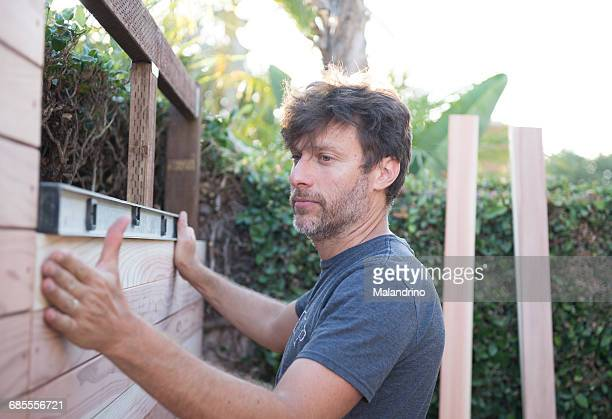 man measuring a fence with tools - initiative stock pictures, royalty-free photos & images