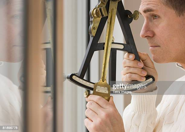 Man measuring angle with sextant