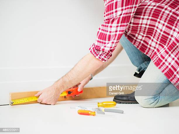 Man measuring baseboard