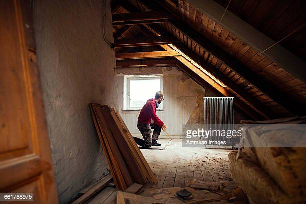 Man measuring floor with tape measure in attic under renovation