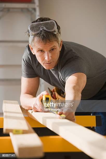 Man measuring piece of wood