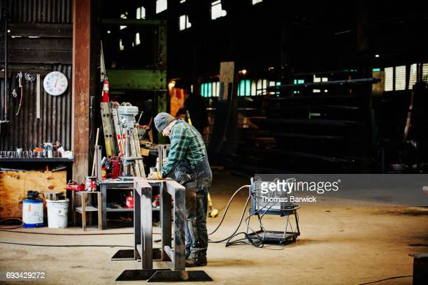 Man measuring sheet metal in workshop before cutting for project