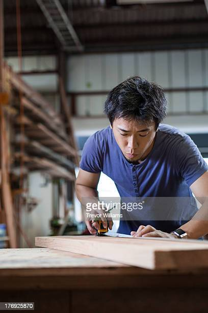 A man measuring something on a piece of wood