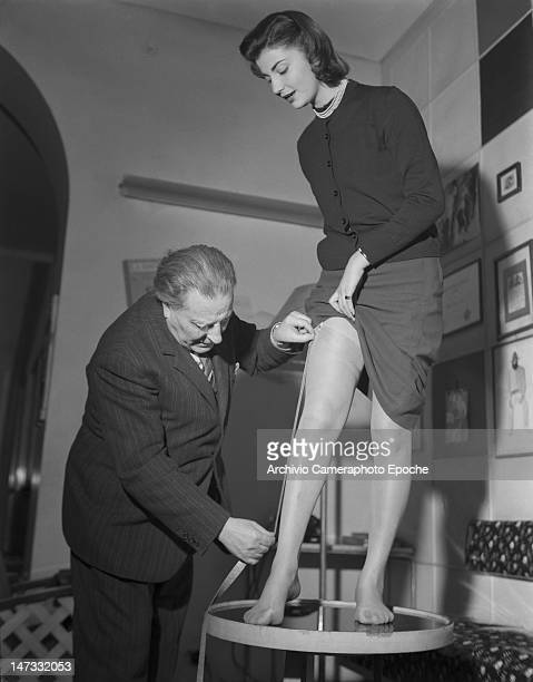 A man measuring tights on a model standing on a table Museum of Famous Tights Milan 1950