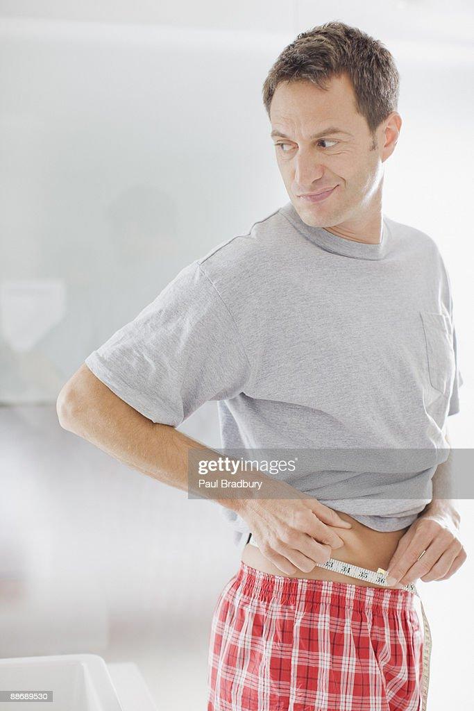 Man measuring waistline : Stock Photo