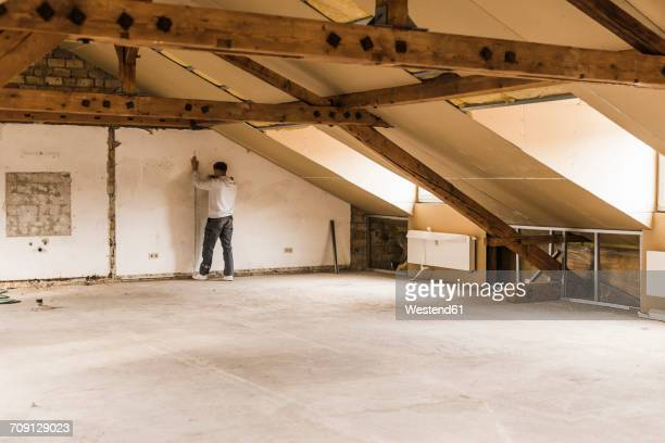 Man measuring wall on construction site