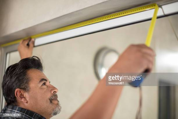 man measuring window frame - instrument of measurement stock pictures, royalty-free photos & images