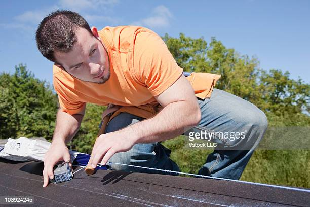Man measuring with chalk dust on roof