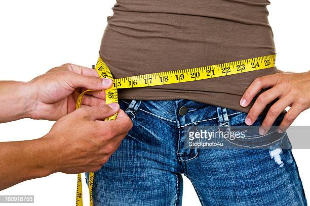 Man measuring woman's waist