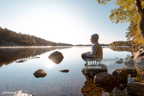 man meditating by the lake after an outdoor exercise - mindfulness stock pictures, royalty-free photos & images