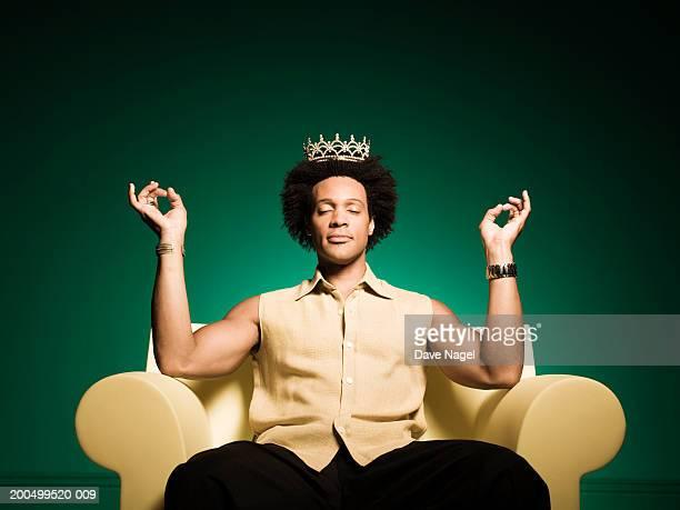 man meditating in armchair, wearing tiarra - corona accesorio de cabeza fotografías e imágenes de stock