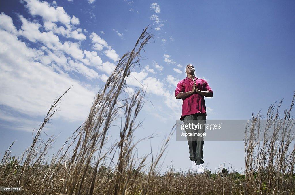 Man meditating in field : Stock Photo