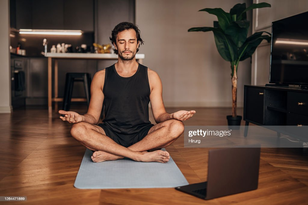 Man meditating in the living room : Stock Photo
