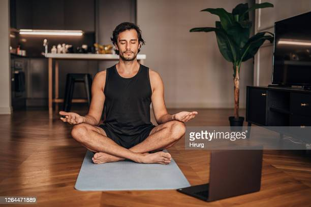 man meditating in the living room - zen imagens e fotografias de stock