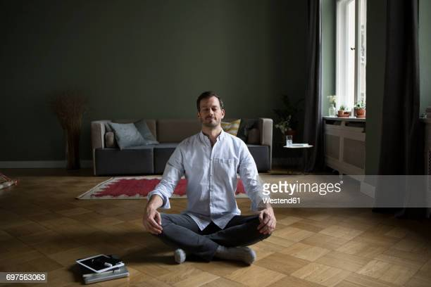 man meditating on the floor at home - meditieren stock-fotos und bilder