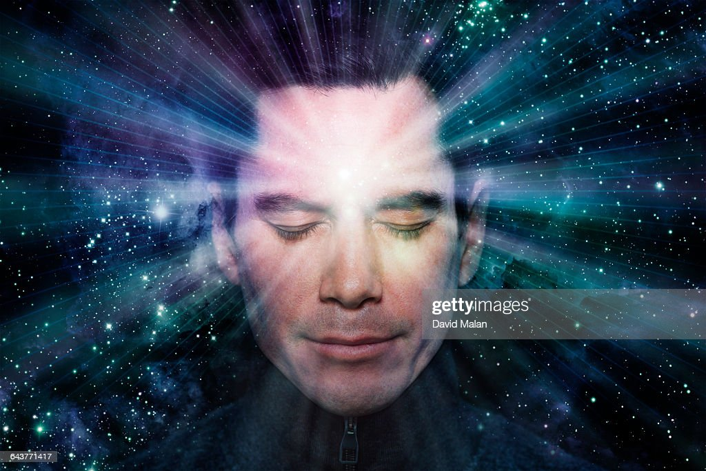 Man meditating with light radiating from him : Stock Photo