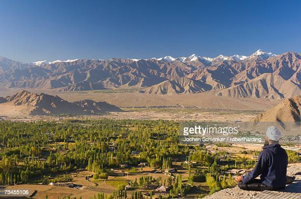 man meditating, with view of indus valley and stok-kangri massif, leh, ladakh, indian himalayas, india, asia - etnia indo asiatica foto e immagini stock