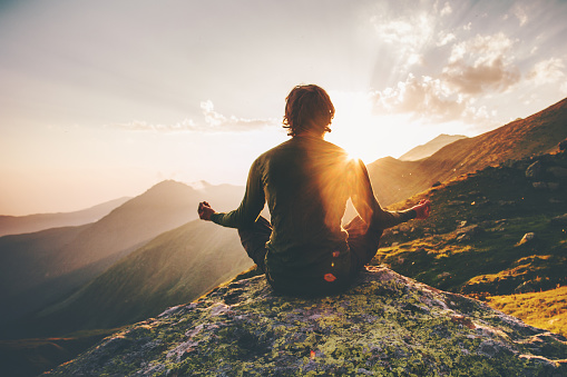 Man meditating yoga at sunset mountains Travel Lifestyle relaxation emotional concept adventure summer vacations outdoor harmony with nature 1028900652