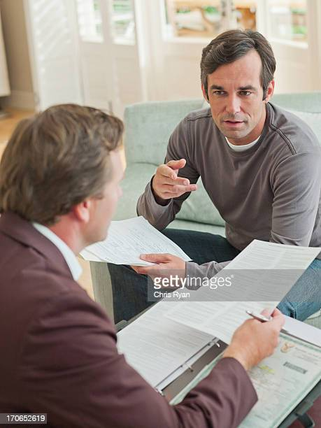 Man meeting with financial advisor in living room